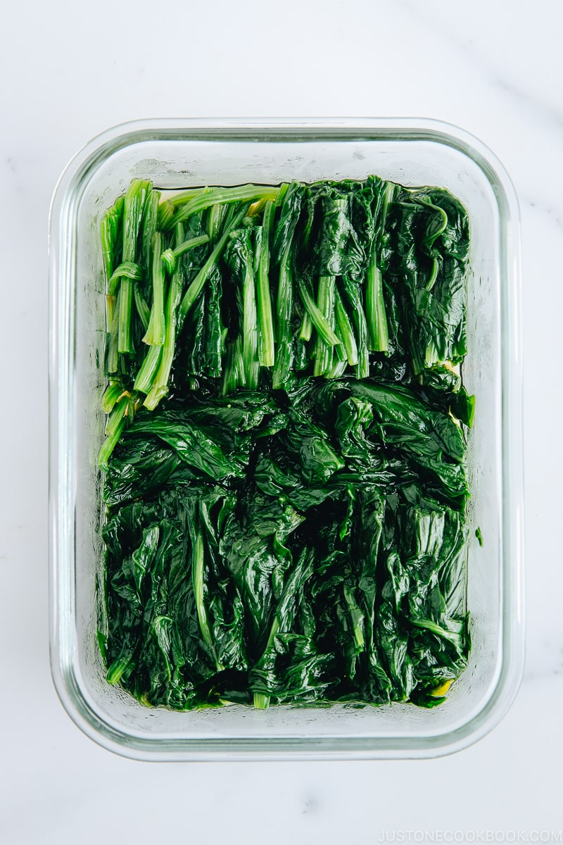 Spinach ohitashi in a glass container.