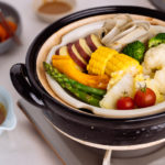 Steamed vegetables on donabe steamer along with dipping sauce.