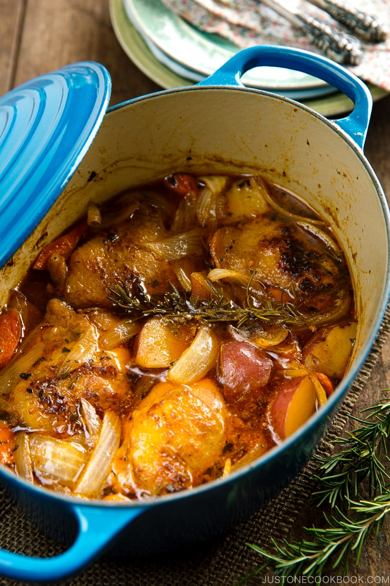 Dutch oven containing braised chicken and vegetables.