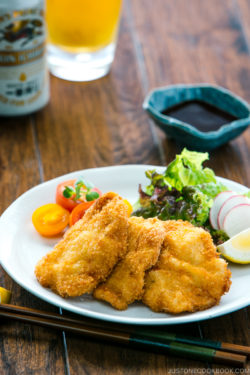 Chicken katsu served on a plate along with spring salad.