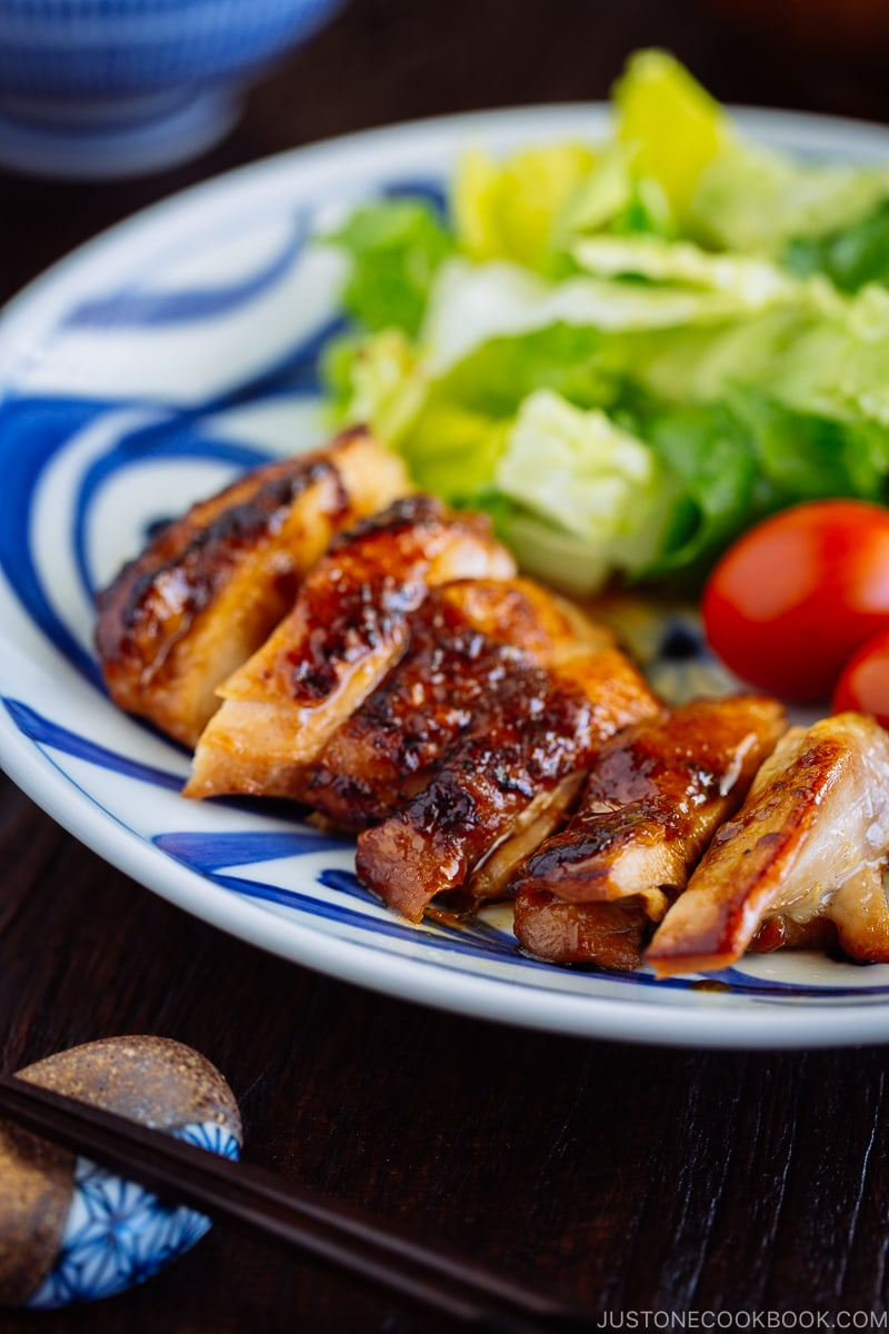 Chicken teriyaki served with salad on a plate.