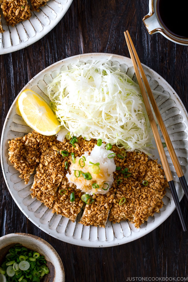 GlutGluten Free Baked Chicken Katsu with cabbage salad and sliced lemon on the plate.