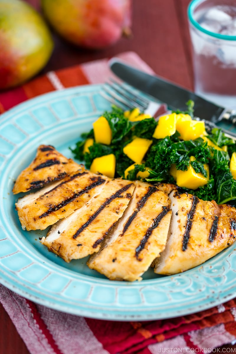 Grilled miso chicken served with Mango Kale Salad on a light blue plate.