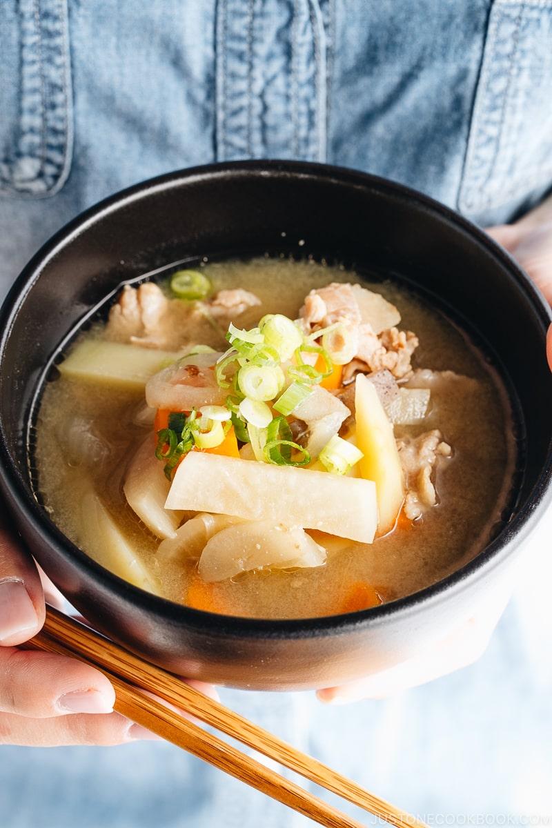 A black bowl containing pork and vegetable miso soup (Tonjiru).