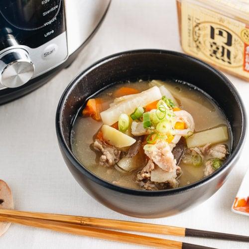 Tonjiru served in a black bowl.