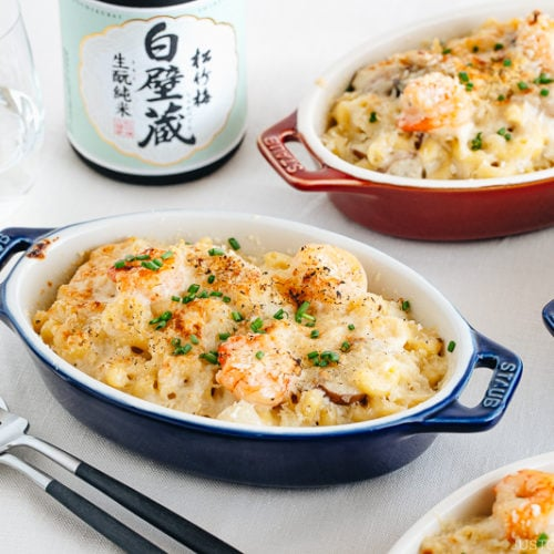 Creamy macaroni gratin served in blue and red STAUB gratin dishes.