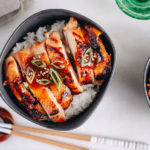 Miso chicken over steamed rice, garnished with sesame seeds and green onion.
