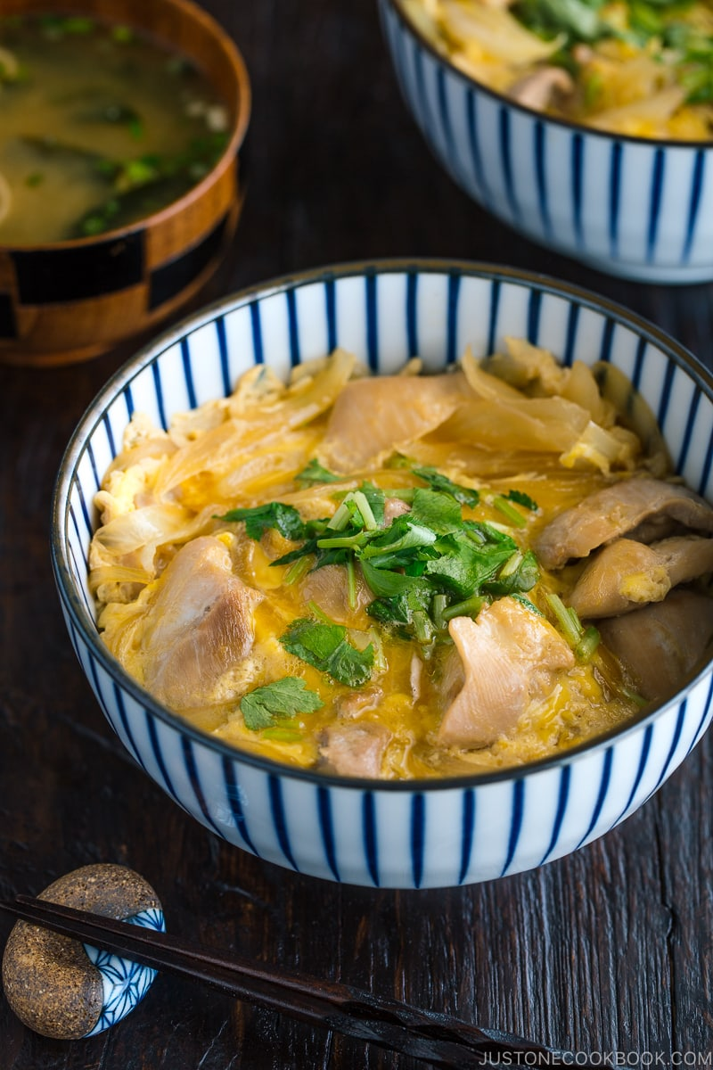 A Japanese blue and white bowl containing Oyakodon (chicken & egg bowl) served with miso soup.