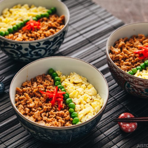 Three Japanese bowls containing seasoned ground chicken, scramble eggs, and green veggies.