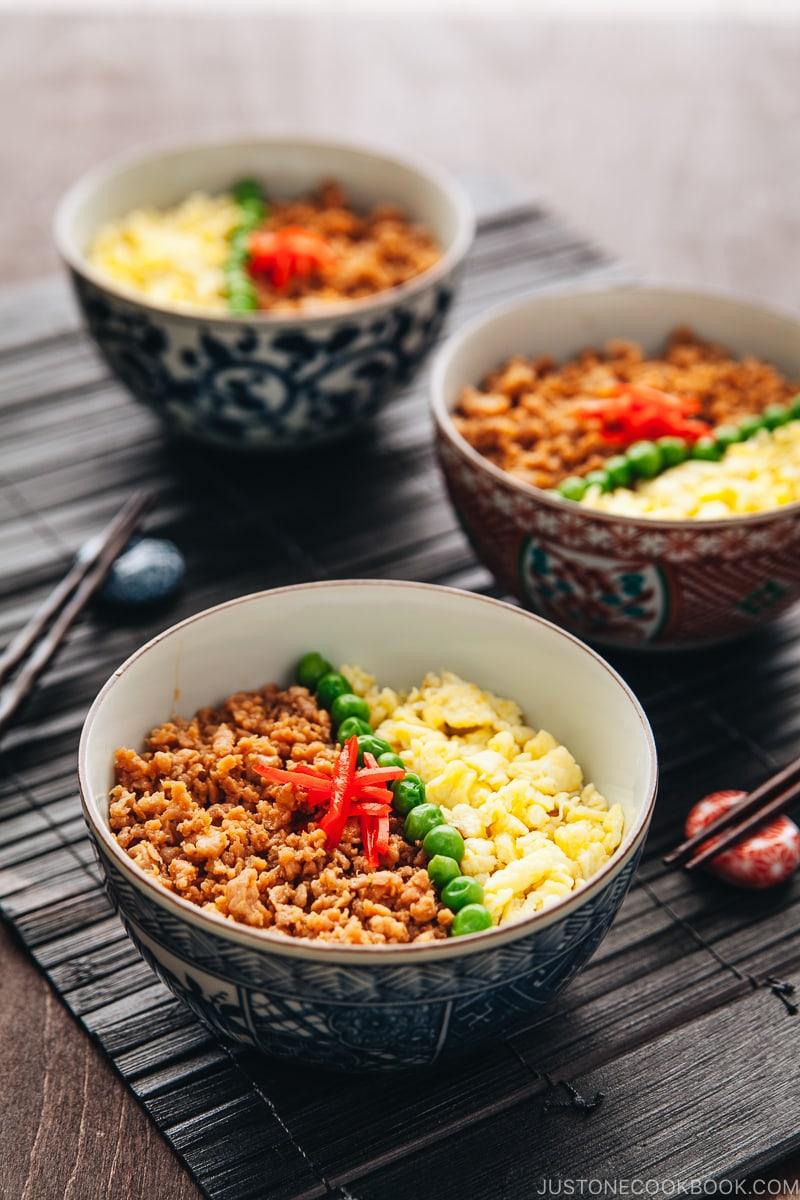 Three Japanese bowls containing seasoned ground chicken, scramble eggs, and green veggies.