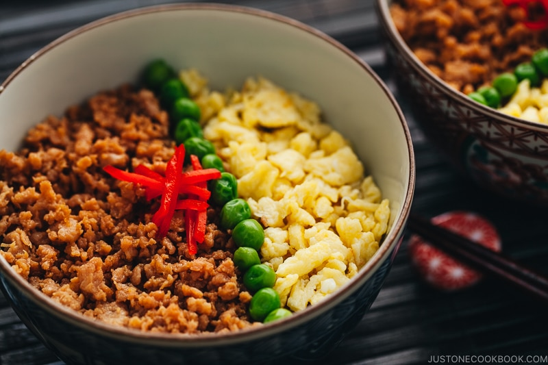 The Japanese bowls containing seasoned ground chicken, scramble eggs, and green veggies.