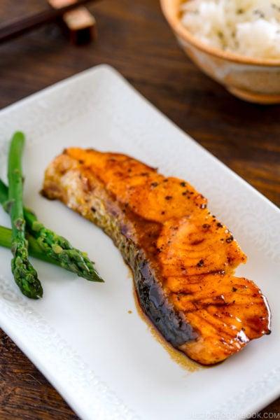 A white plate containing teriyaki salmon with glaze and asparagus.