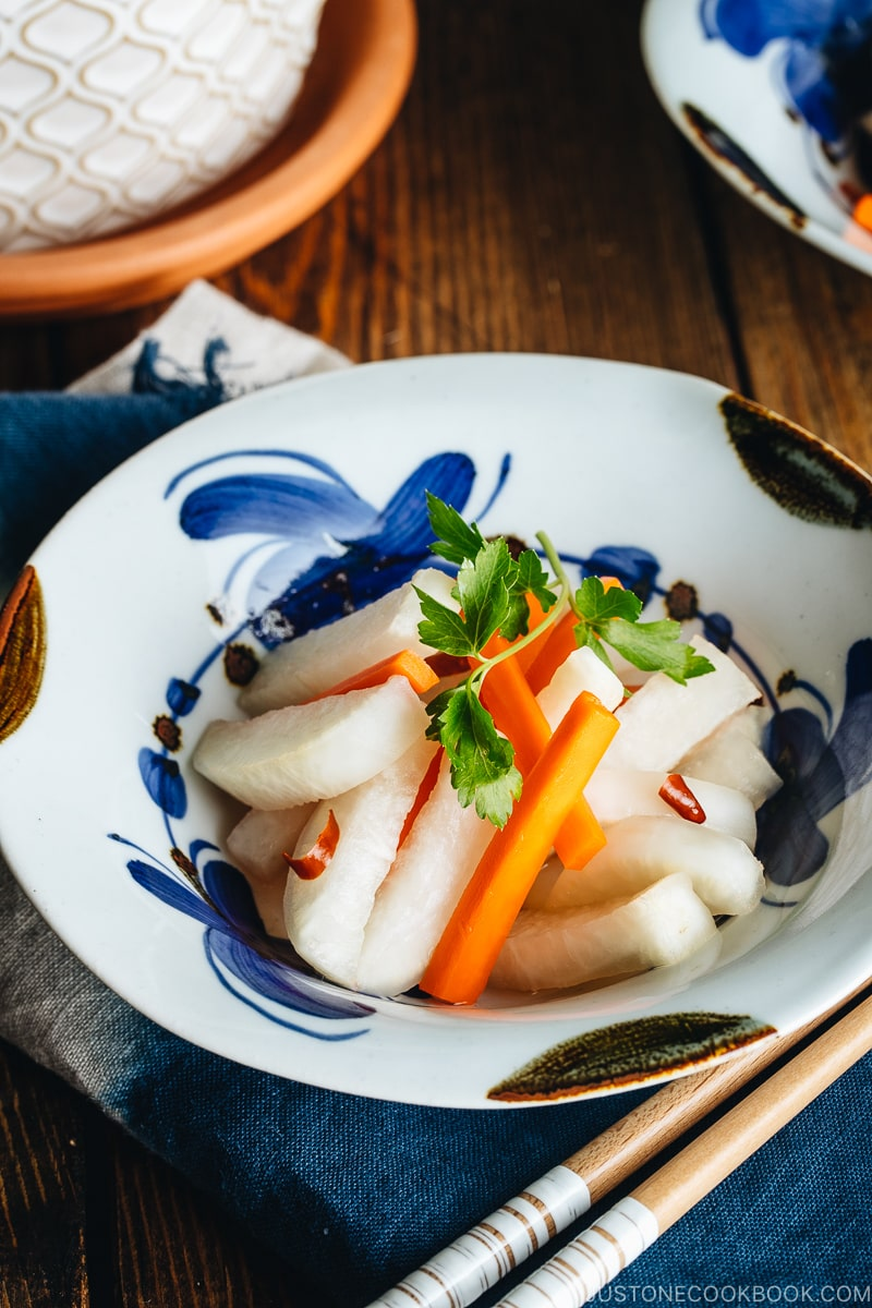 Daikon and carrot pickled in sweet vinegar, served in Japanese ceramic bowls.
