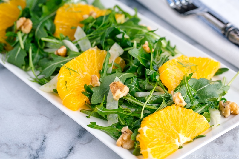 A white rectangular plate containing arugula salad with fennel and navel orange.