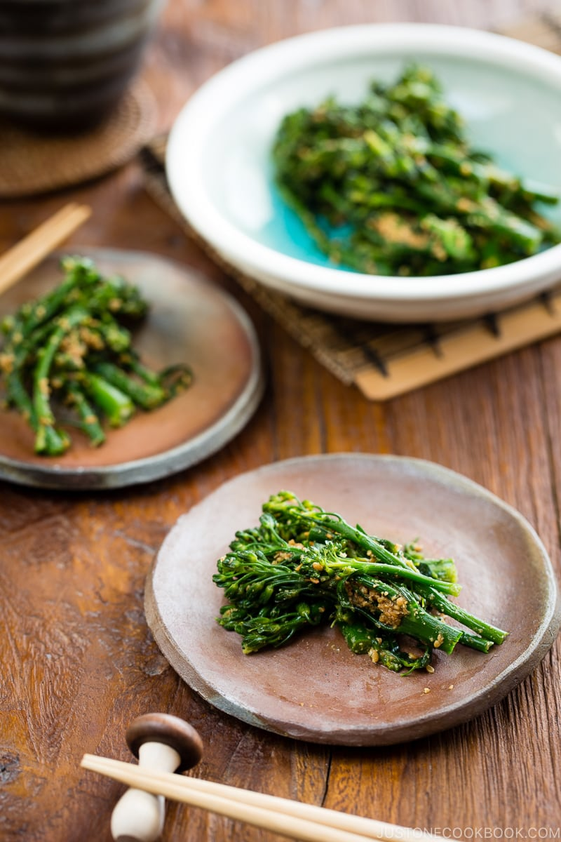 Rustic plates containing broccolini dressed in the Japanese style sesame sauce.