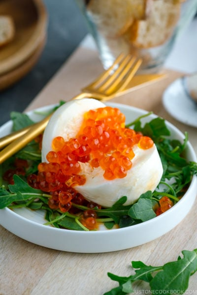 A white plate containing arugula and burrata cheese topped with ikura and served with baguette and yuzu kosho pepper.