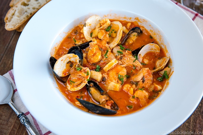 A white bowl containing Cioppino (Seafood Stew) served with rustic bread.