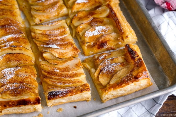 Baking sheet containing apple tart cut into pieces and dusted with powder sugar.