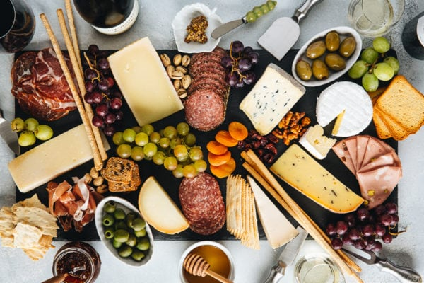 Cheese board filled with cheese, cold cuts, dried fruits, bread sticks, olives, grapes, and condiments.