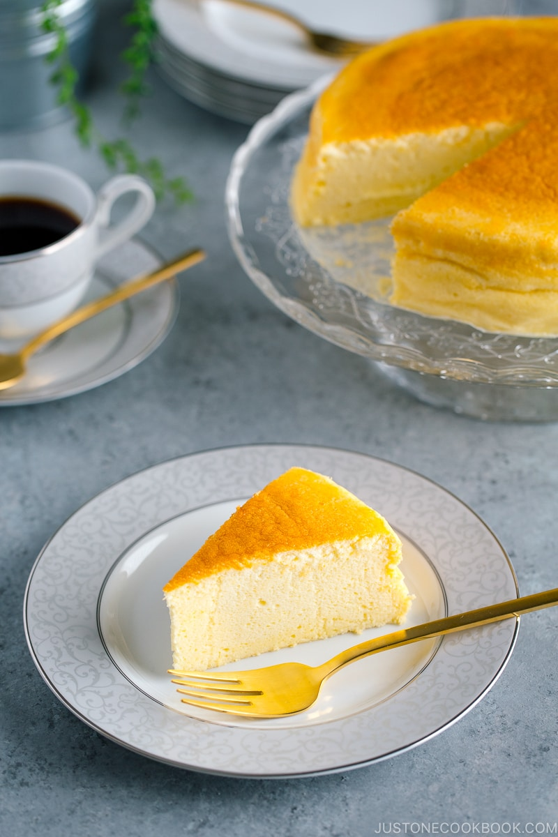 Japanese Cheesecake served on a cake stand and a plate containing a slice.