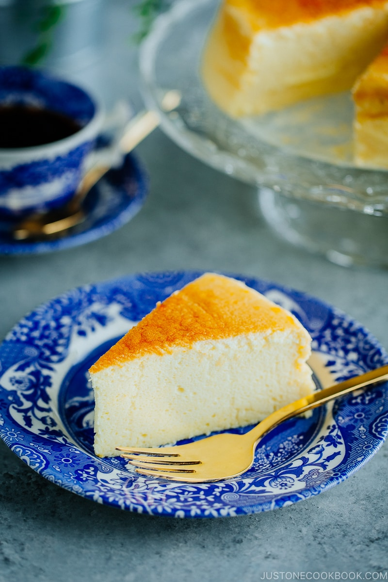 Cheesecake being served on a blue plate.