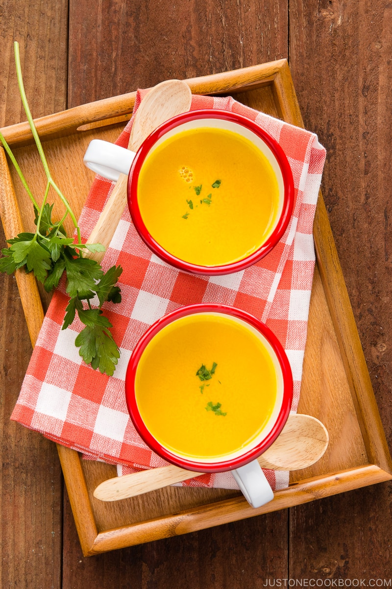 Mug cups containing kabocha soup served on a wooden tray.