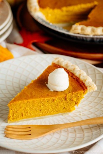 White plate containing a slice of Kabocha Pie topped with freshly whipped cream.