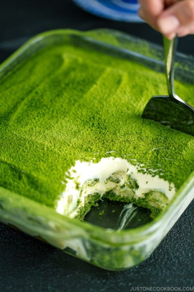 matcha tiramisu cake made with soaked ladyfingers and mascarpone custard filling.