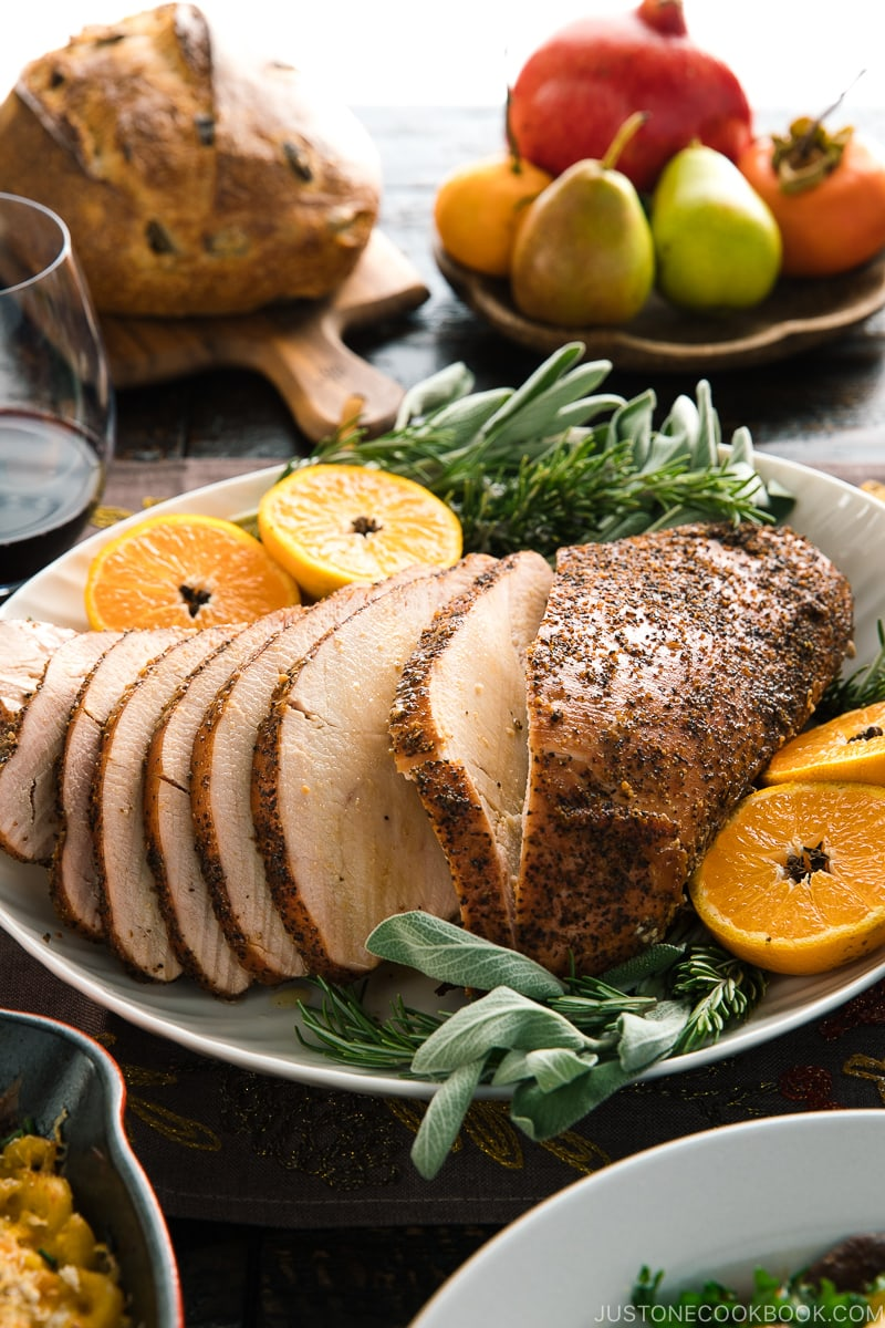 Smoked turkey breast served on a large platter along with tangerine halves and herbs.