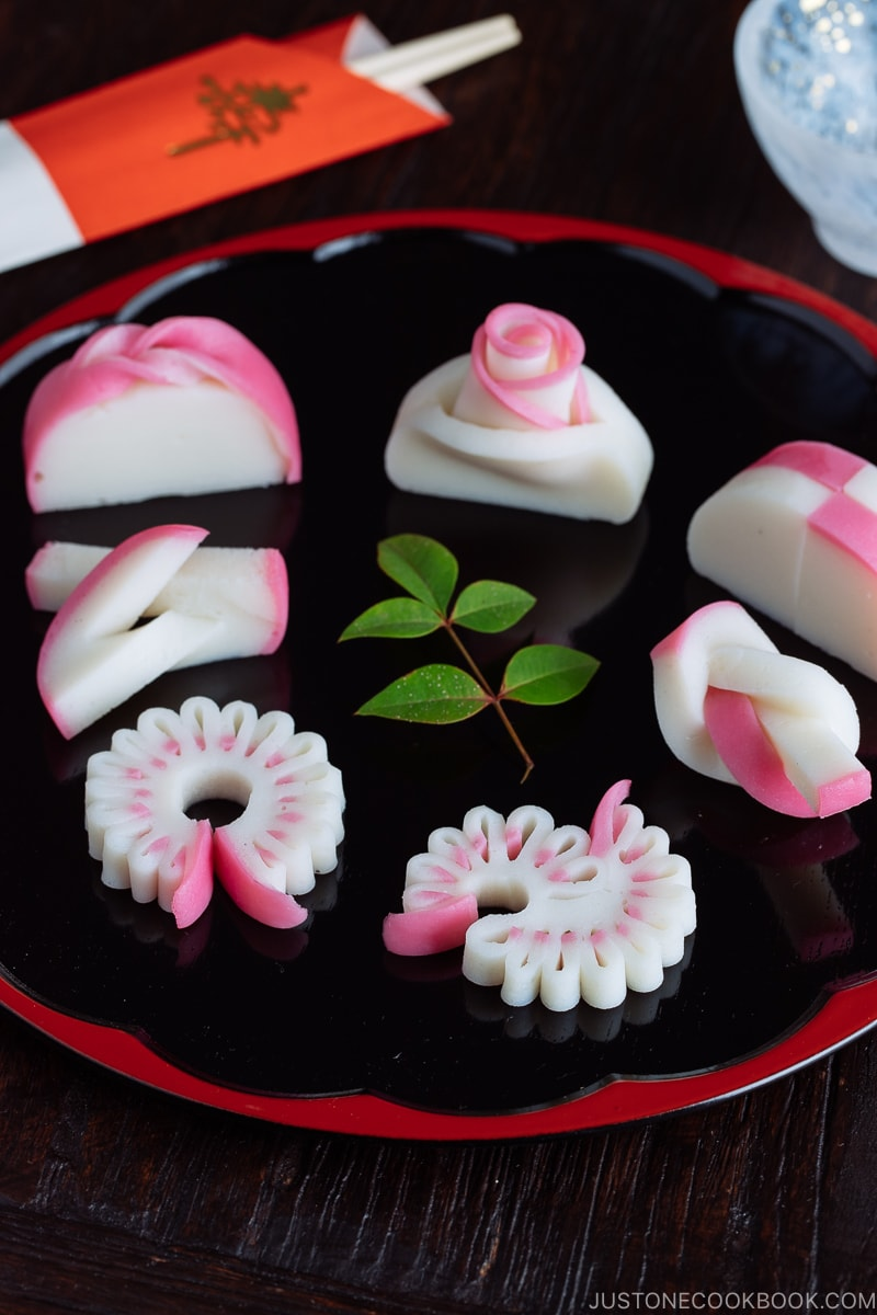 Decorative kamaboko fish cakes on a black and red lacquered board.