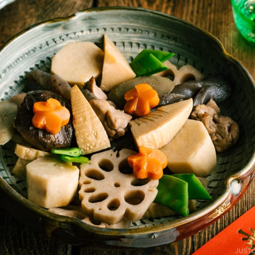 A Japanese ceramic bowl containing simmered chicken and vegetables.