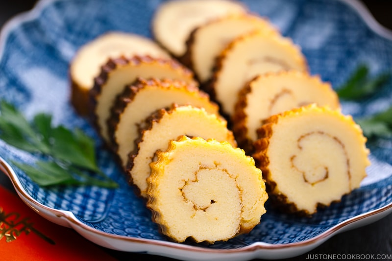 Japanese blue ceramic plate containing slices of Datemaki (Sweet Rolled Omelette)