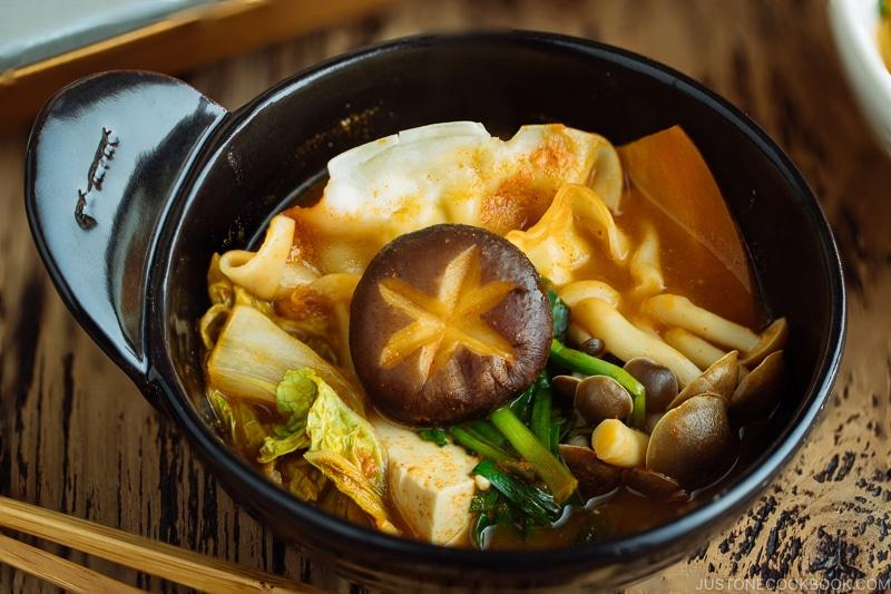 A donabe hot pot containing kimchi gyoza hot pot stew.