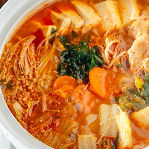 A Japanese donabe containing kimchi stew filled with vegetables and kimchi.