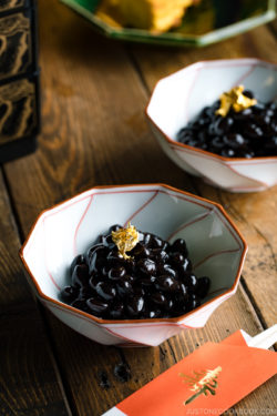 A white and red Japanese bowl containing Kuromame, sweet black soybeans, topped with gold leaf for the Japanese new year's celebration.