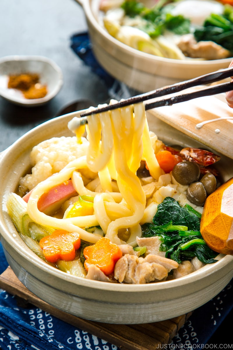 Donabe containing udon noodles, chicken, fish cake, mushrooms, and vegetables in a flavorful soup broth