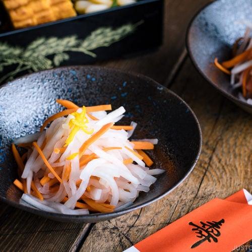 A black bowl containing Namasu (Japanese Daikon and Carrot Salad).