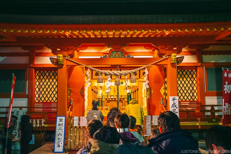 A group of people standing in front of a shrine