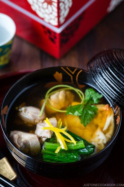 A black and gold lacquered bowl containing Japanese New Year Soup Ozoni.