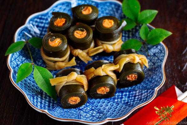 A blue Japanese plate containing salmon kombu rolls.
