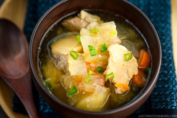 Pork and vegetable miso soup in a wooden bowl.