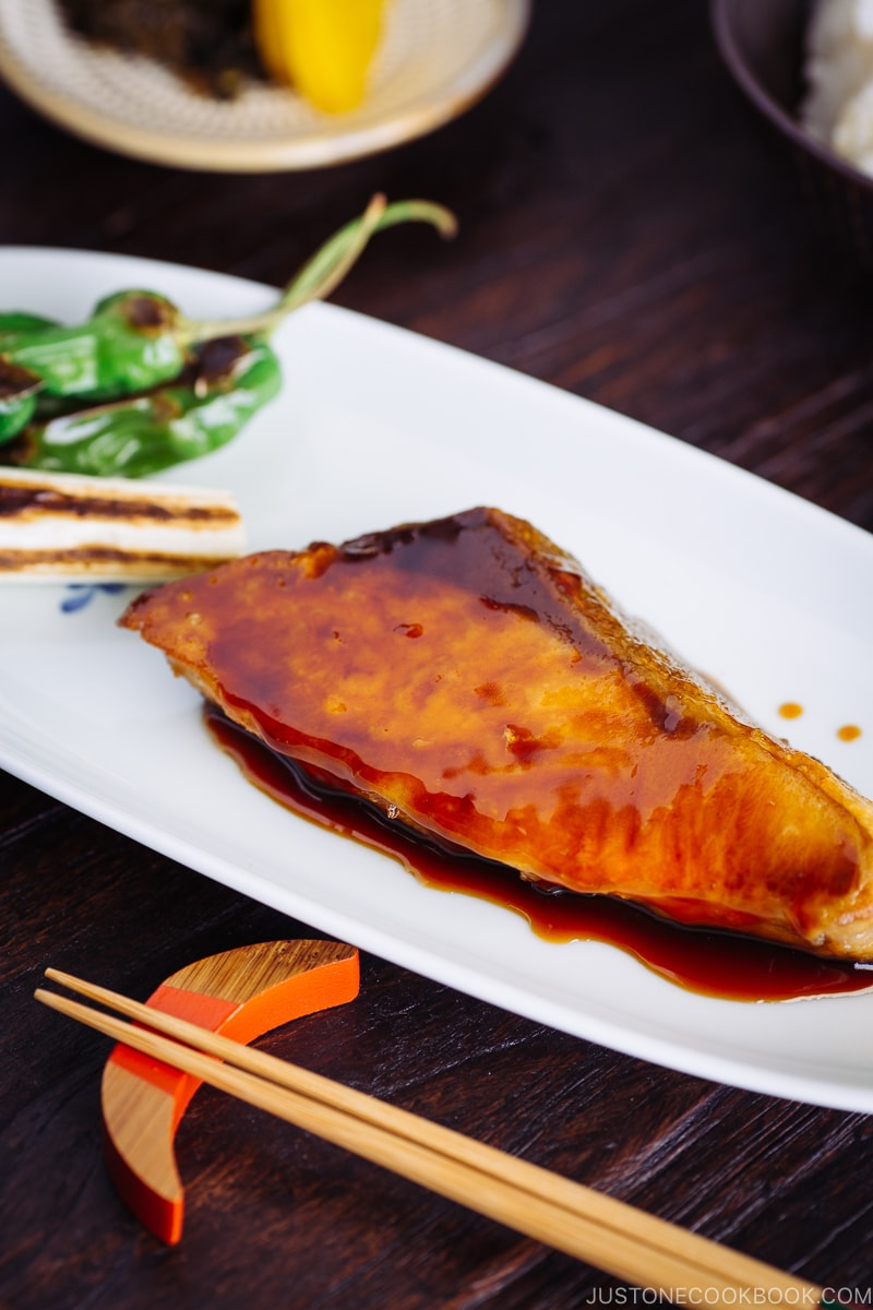 Yellowtail teriyaki served with blistered shishito peppers.