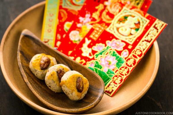 Chinese almond cookies and red envelops on a wooden tray.