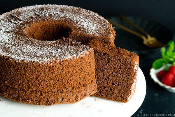 A chocolate chiffon cake served on a cake stand.