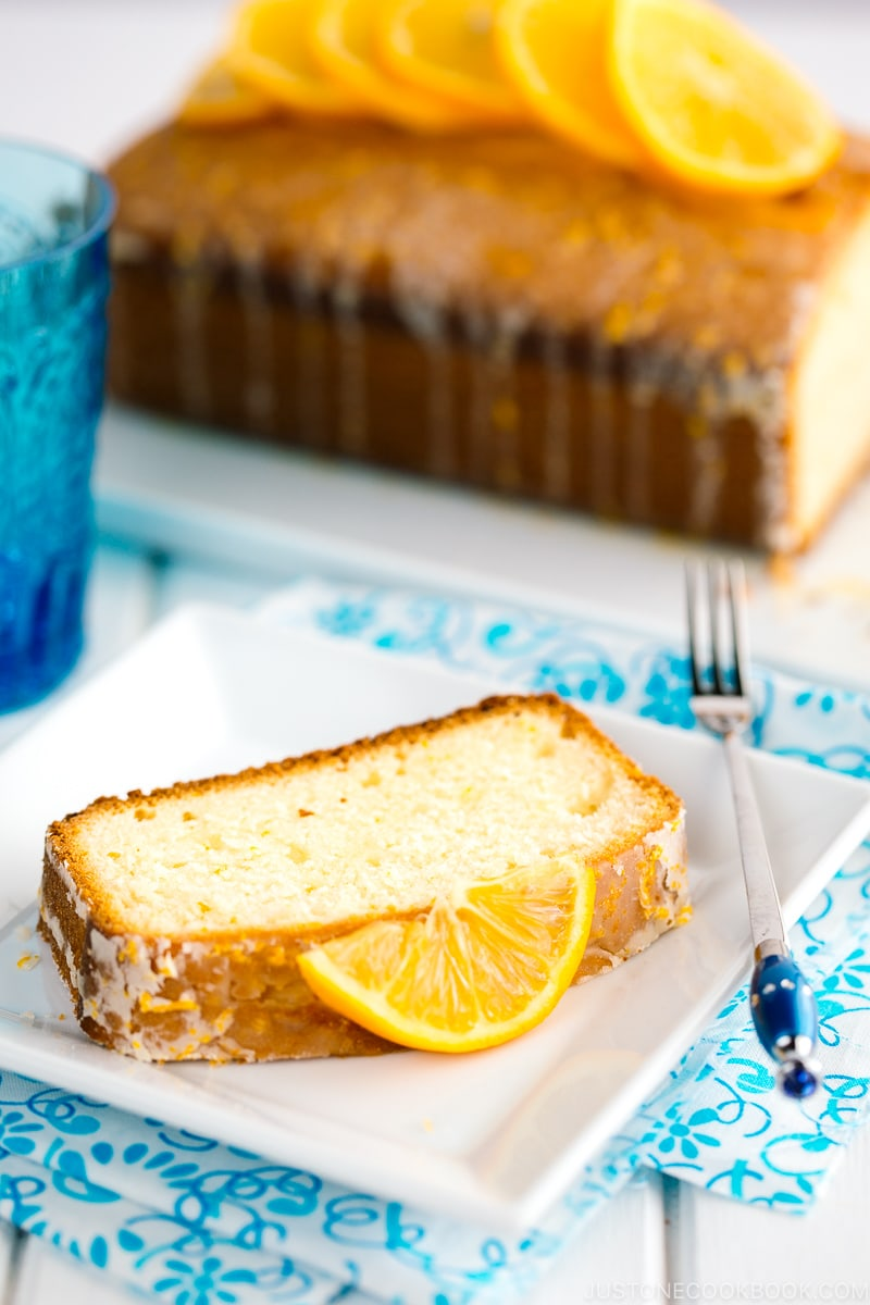 A slice of Meyer Lemon Pound Cake is on white plate.