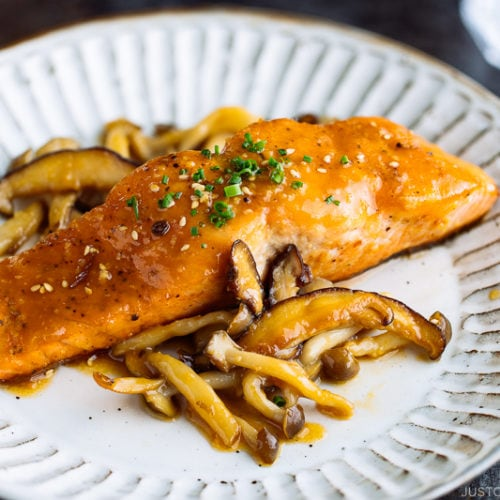 A white plate containing Miso Butter Salmon served with sautéed shiitake and shimeji mushrooms.
