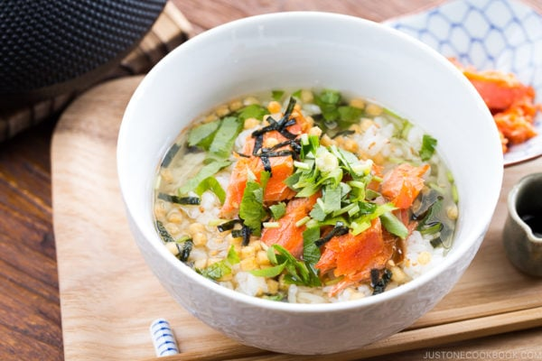 Japanese tea is poured on top of steamed rice and flaky baked salmon in a rice bowl.