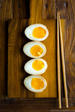 Ramen eggs (Ajitsuke Tamago) on a wooden cutting board.