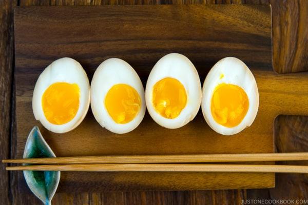 Ramen eggs (Ajitsuke Tamago) on a wooden cutting board.