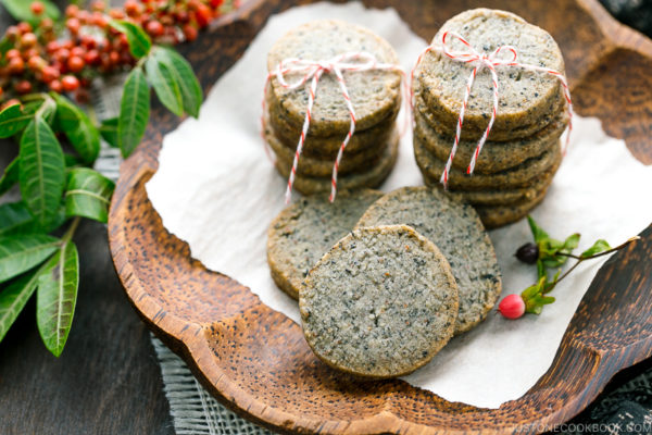 The wooden plate containing black sesame cookies.